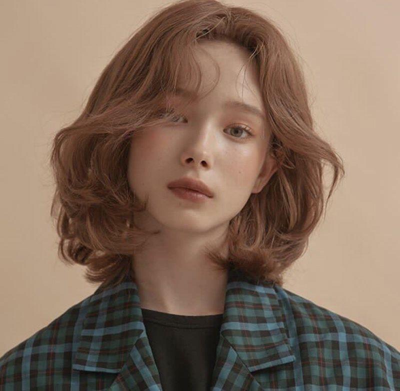 Kiểu tóc xoăn sóng ngắn rẽ ngôi giữa giúp khuôn mặt thanh thoát hơn